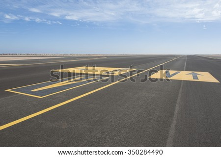Directional sign markings on the tarmac of runway at a commercial airport