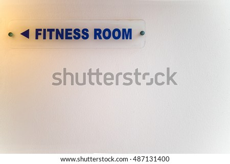 Directional sign to fitness room on white wall. Healthy concept.