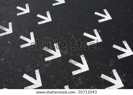 directional white arrow signs on the asphalt road - stock photo