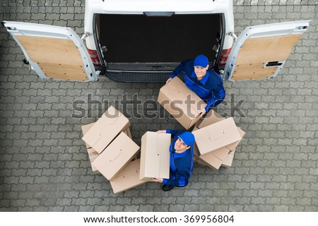 Directly above portrait of delivery men carrying cardboard boxes outside truck on street - stock photo
