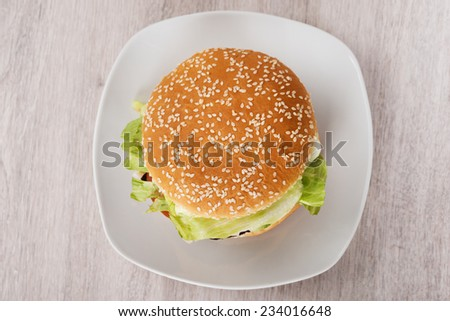 Directly above shot of burger in plate on floor - stock photo