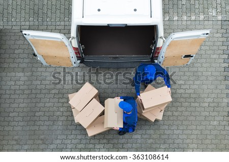 Directly above shot of delivery men unloading cardboard boxes from truck on street - stock photo