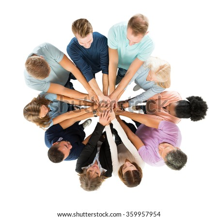 Directly above shot of people stacking hands while standing against white background