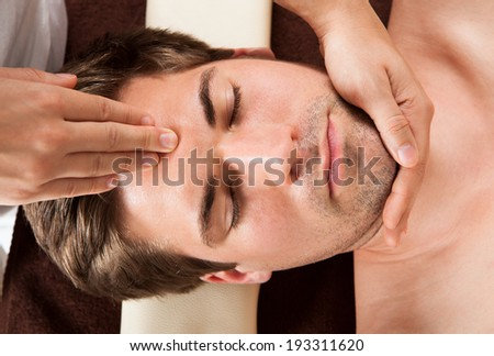 Directly above shot of relaxed young man receiving forehead massage in spa