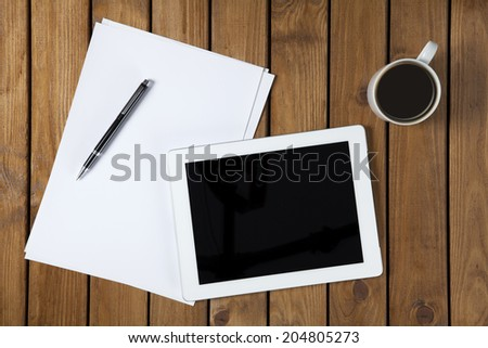 Directly above view of a old wooden table, pen, papers and tablet pc on it.