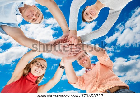 Directly below portrait of friends stacking hands while standing in huddle against sky