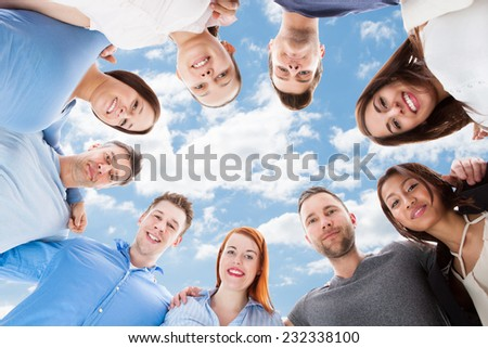 Directly below portrait of happy multiethnic friends forming huddle against sky