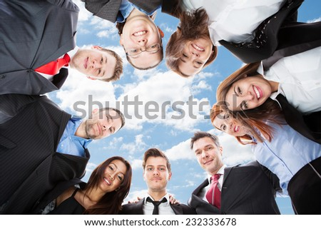 Directly below portrait of multiethnic businesspeople forming huddle against sky