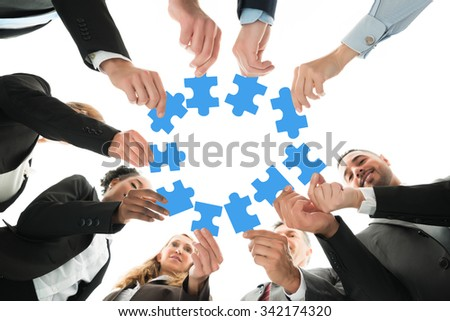 Directly below shot of business team joining jigsaw pieces in huddle against white background - stock photo