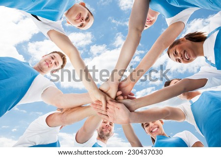 Directly below shot of diverse professional cleaners piling hands against sky - stock photo