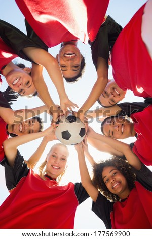 Directly below shot of female soccer team with ball forming huddle against clear sky - stock photo