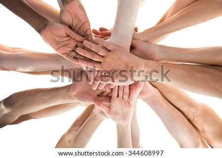 Directly below shot of janitors stacking hands against white background