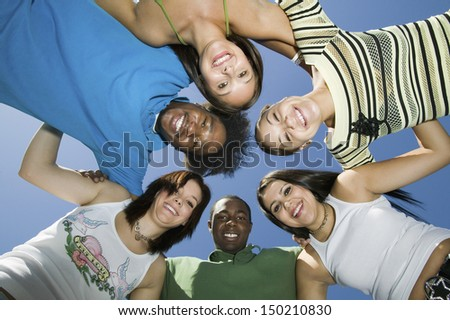 Directly below shot of young friends forming huddle against blue sky - stock photo