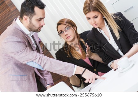 Director finger pointing at paper document, and female are surprised.