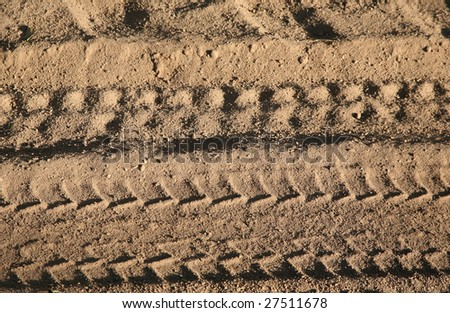 Dirt background with vehicle pattern track