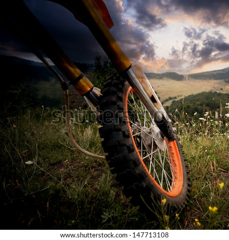 dirt bike close-up details over the scenic HDR sunset - stock photo