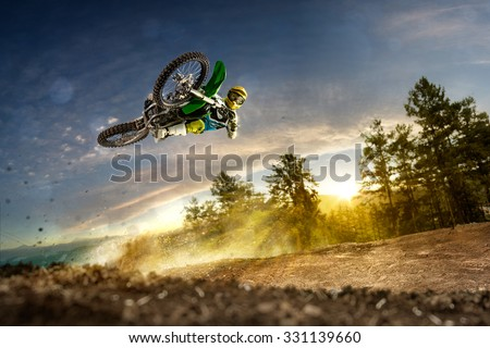 Dirt bike rider is flying high in evening - stock photo