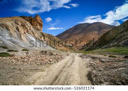 Dirt gravel mountain road through the high central Tibetan plateau, Tibet, China