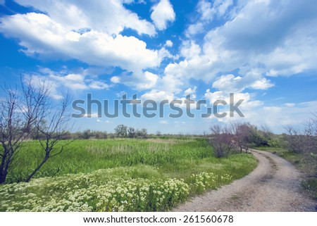 Dirt road and clouds in the sky - stock photo