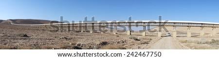 Dirt road and long conveyor in Negev desert, Israel                                - stock photo