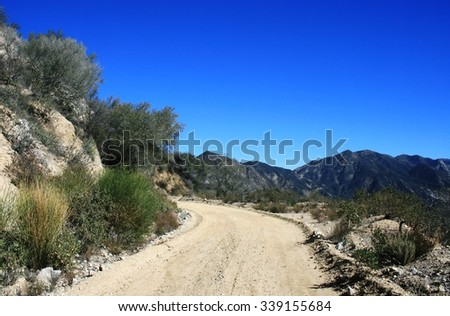 Dirt road ascending a hill side, Angeles National Forest, CA - stock photo