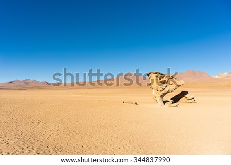 Dirt road at high altitude with sandy desert and scenic rock formation on the Andean highlands. Road trip to the famous Uyuni Salt Flat, among the most important travel destination in Bolivia. - stock photo