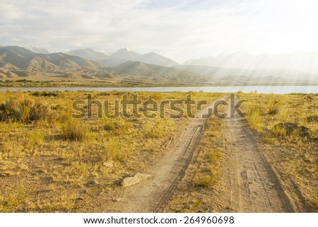 Dirt road in a mountain lake - stock photo