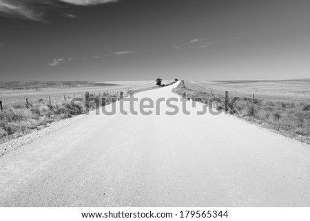 Dirt road in country Australia stretches into the distance under a blue sky in black and white - stock photo