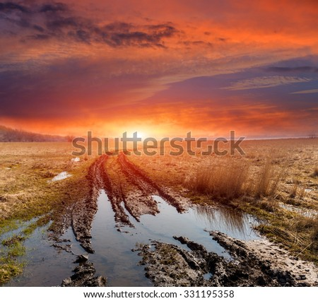 dirt road in spring steppe after rain against sunset background - stock photo