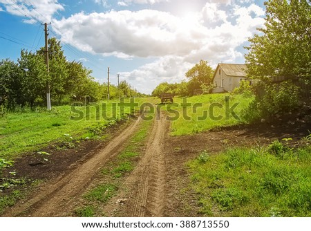 Dirt road in the village, spring day and green grass around. Power poles in the village along the road. Rural landscape - May in Ukraine.