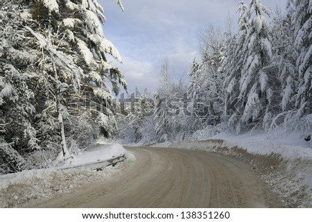 Dirt road leading between snow covered trees, Stowe, Vermont, USA - stock photo