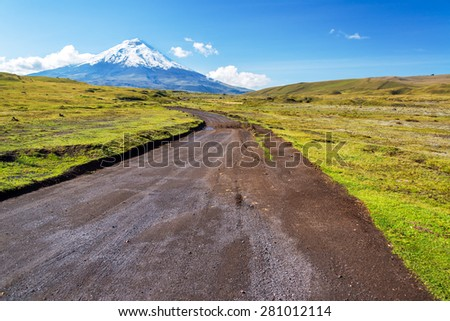 Dirt road leading to snow capped Cotopaxi Volcano in Ecuador - stock photo