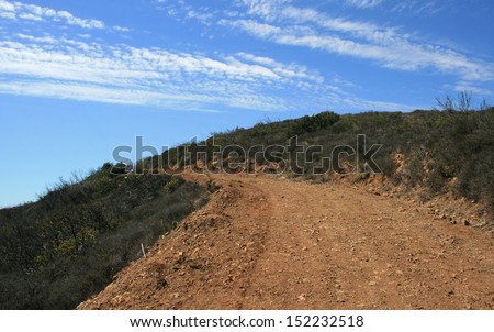 Dirt road leading up a hill side beneath blue sky with clouds, Malibu, CA - stock photo