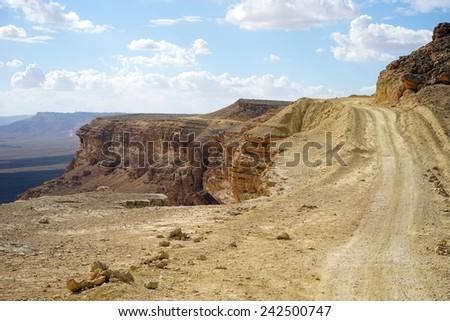 Dirt road on the edge of crater Ramon in Negev desert. Israel