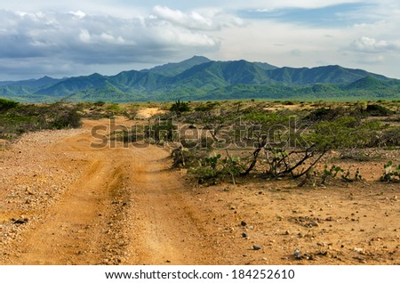 Dirt road passing through a desert with the lush green hills of Macuira National Park visible in the background in La Guajira, Colombia - stock photo