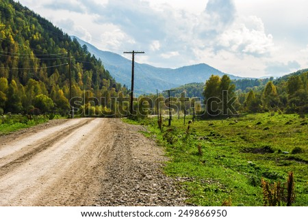 Dirt road stretches into the distance in the mountains. - stock photo