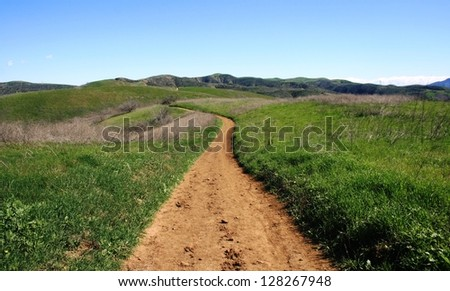 Dirt road through hills and green fields in a state park, California - stock photo