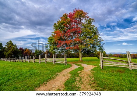 Dirt road through split rail fence in the Cumberland Gap National Park - stock photo