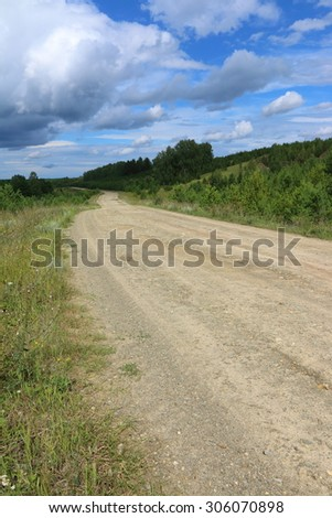 Dirt road to a remote village against a cloudy sky - stock photo