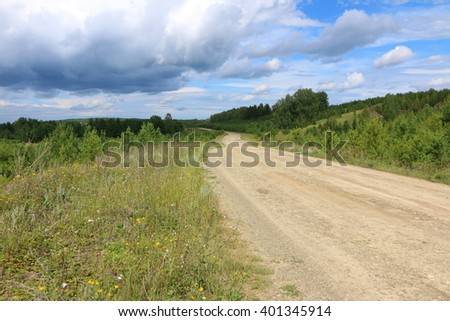 Dirt road to a remote village against a cloudy sky