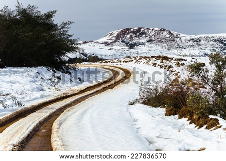 Dirt Road Tracks Snow Mountains Dirt road tracks over  high plateau mountain terrain in winter snow scenic landscape - stock photo
