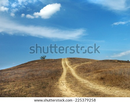 dirt road up the hill and blue sky - stock photo