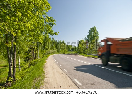 Dirt road with asphalt dump truck in motion - stock photo