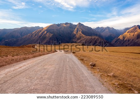 Dirt road with the Andes mountains rising the background in the Sacred Valley near Cusco, Peru - stock photo