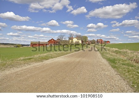 Dirt track through agricultural land in spring - stock photo