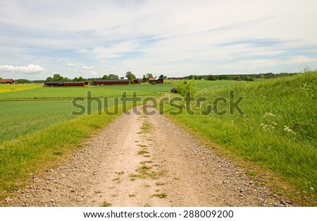 Dirt track through agricultural landscape in summer - stock photo