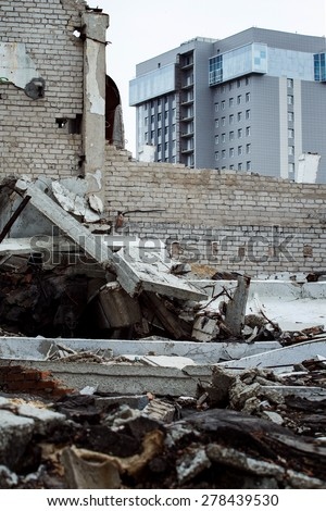 Dirty abandoned trash ruins with modern office building at background. Concept of old and new contrast, rich and poor. - stock photo