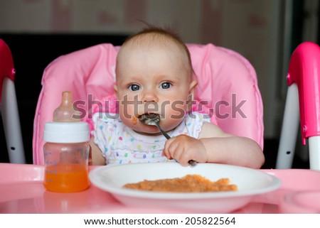 dirty baby girl eating dinner - stock photo