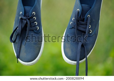 Dirty Blue Sneakers on Clothes Line - stock photo