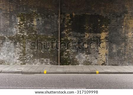 Dirty brick wall under the bridge. - stock photo
